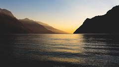 Golden reflections (Nicola Pezzoli) Tags: italy lake garda lago riva trentino nature reflections sunset colors mountain silhouette water beach