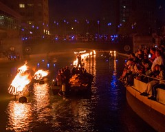 Fire Dancer performs on a wood boat (Photograph by Drew Christhilf) (waterfireprov) Tags: bridgeofstars cirquedelight crowd dreamorb emberflame firedancer woodboat