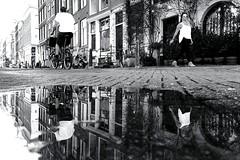 doppelt gemoppelt (ploh1) Tags: amsterdam pfütze spiegelung perspektive stadtansicht menschen leute personen wasser niederlande frau mann radfahrer regenpfütze häuser häuserreihe innenstadt sw bw schwarzweiss
