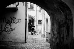 Way back (lorenzoviolone) Tags: arch bw bicycle bike blackwhite blackandwhite candid d5200 dslr ilforddelta3200 monochrome nikon nikond5200 reflex cobblestone event2017saintanthony filmborn mastinlabs stranger streetphoto streetphotobw streetphotography walk:trevignano=jan2017 trevignanoromano lazio italy