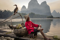 Cormorant Fisherman in XingPing (lycheng99) Tags: xingping fisherman cormorant cormorants cormorantfisherman cormorantfishing bambooraft bamboo man chinese red traditional river liriver líjiāng lijiang reflections sunset bird guilin guangxi china chinatravel travel asia