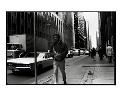 Man walking, carrying gloves and a large envelope (Richard C. Johnson: AKA fishwrapcomix) Tags: nikonf nikkor35mm kodakplusx scanfromfilm negative film analogue analog blackandwhite monochrome bw nyc 1978 manhattan archive mybackpages ishotfilm ishootfilm filmisnotdead 1970sarchive reallyoldcrap whenfilmwasking newyorkcity bigapple street people outdoor pedestrians cars sidewalk