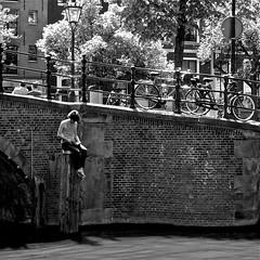 Pole Sitter (Akbar Simonse) Tags: bridge boy people bw man holland blancoynegro netherlands monochrome amsterdam square reading book canal boek zwartwit candid nederland bn bicycles brug mokum fietsen lezen polesitter akbarsimonse paalzitter