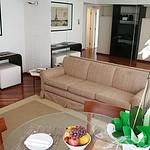 Sofás e tapetes no mesmo tom. Um enorme espelho atrás do sofá amplia o espaço