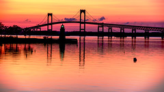 Goat Island Lighthouse at Sunset (Ian Charleton) Tags: goatislandlighthouse pellbridge newportbridge newport rhodeisland reflection sunset sky water coast shore coastline seascape cpf lighthouse bridge architecture