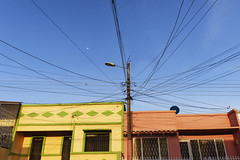 Slice and dice (Michael Evans) Tags: michaelevansphotography fujifilm fujifilmxe2 xe2 photography photo photograph foto fotografia color blue yellow green red pink peach black powerlines powercables electricalcables electricity sky clearsky moon houses colombia libano tolima southamerica latinamerica cable line slice