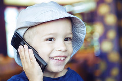 happy boy on the phone (studioimagonis) Tags: boy portrait hat childhood smiling closeup happy holding child cellphone headshot indoors browneyes littleboy oneperson lookingaway partof toothysmile childrenonly