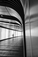 Kings Cross St Pancras Light Tunnel (B&W) (Nick Biswell) Tags: unitedkingdom greaterlondon london stpancrasinternational photo242015 kingscross onepancrassquare alliesmorrison speirsmajor thelightlab tunnel concourse light lights lighting sony sonydslra580 sonya580 tamron tamron1935 tamronaf1935mmf3546a10 person ghost ghostly blur slow slowshutterspeed blackandwhite monochrome niksoftware silverefexpro