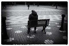 Solitary (halifaxlight) Tags: england birmingham man sitting alone bench pedestrians dark urban plaza patterns bw