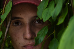 (Taran W) Tags: red hat green leaves plants outdoor light shadows people portrait face freckles