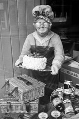 Grannie (Man with Red Eyes) Tags: trix kodak hc110 leicam2 summicron35mmf2 iv v4 analog blackwhite monochrome silverhalide sunnysixteen northumberland northumbria alnwick grannie shopwindow shopdisplay cake glasses spectacles