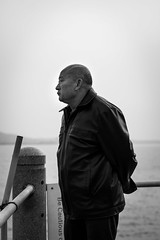 Mind traveler (Go-tea 郭天) Tags: qingdaoshi shandongsheng chine cn qingdao huangdao man old alone lonely sea water day sun sunny facing side observation observing think thinking stand standing lost immobile portrait candide candid unknown questions answers find dinding look looking research profile coat bold canon eos 100d 50mm prime street urban city outside outdoor people bw bnw black white blackwhite blackandwhite monochrome naturallight natural light asia asian china chinese shandong