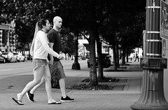 Casual Date (burnt dirt) Tags: houston texas downtown city town mainstreet sidewalk street corner crosswalk streetphotography xt1 fujifilm bw blackandwhite girl woman people person cutoffs shorts sandals man couple pair longhair walking ponytail tree asian