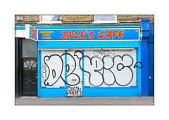 Street Art (Unknown), East London, England. (Joseph O'Malley64) Tags: unknown streetart urbanart publicart freeart graffiti eastlondon eastend london england uk britain british greatbritain art artist artistry artwork cafe shopfront victorianbuilding victorianstructure shutter rollershutter defaced defacement signs signage stucco stuccowork mouldings brickwork bricksmortar cement pointing windows leadflashing roofingfelt wiring junctionboxes woodwork doorway woodendoor entrance exit steelsecuritymesh frostedglass tarmac secure padlocks padlocked urban urbanlandscape aerosol cans spray paint fujix accuracyprecision