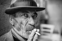 Cigarette, hat and chai (Giulio Magnifico) Tags: life lighting light man eye smile look hat closeup composition contrast vintage turkey interesting intense emotion expression cigarette character smoke citylife streetphotography streetportrait smoking sharp elder syria aged smoker gaze glance chai gaziantep nikond800e sigma35mmf14dghsm