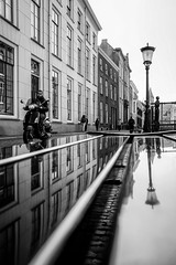 Utrecht reflections with scooter (PaulHoo) Tags: utrecht holland city urban fujifilm fuji x70 2017 reflection street candid streetphotography line lantern building architecture museumkwartier bw blackandwhite monochrome man scooter transportation bench