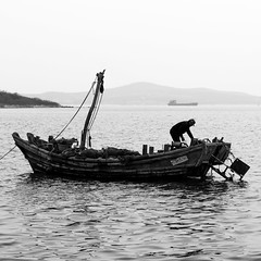An other departure (Go-tea 郭天) Tags: qingdao huangdao man alone lonely boat ship sea water side navigate navigator capture work business duty working fisherman fish preparing prepare preparation getting ready old sail sailing canon eos 100d 50mm prime street urban city outside outdoor people bw bnw black white blackwhite blackandwhite monochrome naturallight natural light asia asian china chinese shandong qingdaoshi shandongsheng chine cn hat board