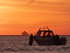 I'm confused, isn't the idea to be inside the boat (Peanut1371) Tags: cleethorpes sunrise sky orange sea fort boat man