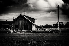 rustic yet modern (Christian Collins) Tags: canoneosrebelt2i ef70200mmf4lusm wisconsin hicontrast barnwood modern car house windmill pole evening bw blacknwhite black white