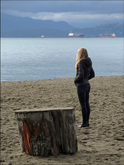 A good place for deep thoughts (HereInVancouver) Tags: englishbay ocean water pacific beach freighters coastmountains log youngwoman contemplation deepthoughts lookingouttosea thingstodobythewater candid canong3x vancouver bc canada vancouverswestend