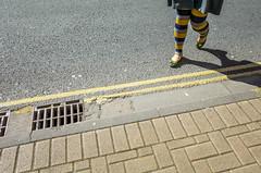 Bristol; April 2017 (Daniel Durrans) Tags: doubleyellowlines urban legs yellow road street bristol leggings streetphotography gutter drain stripyleggings pavement stripy