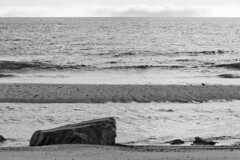 Erratic on the Tide (brucetopher) Tags: beach water sea ocean clouds weather peace peacefull surf sand break shore coast coastal fog fogbank rock glacial glacier iceage remnant rubble stone boulder black white blackandwhite bw blackwhite monochrome contrast tone tones 7dwf