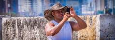 2014 - Cartagena Columbia - Tourist - 1 of 3 (Ted's photos - For me & you) Tags: camera portrait male face muscles hat hands nikon colombia photographer arms teeth cellphone shooting cartagena retainingwall aiming brim d600 cartagenacolombia simplysuperb tedsphotos nikonfx