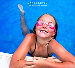 Little girl in pool with goggles (Marco Govel) Tags: pink blue summer portrait people cute wet water pool girl beauty smile face childhood sport swim fun happy person one glasses kid healthy child play little joy goggles lifestyle happiness swimmingpool cap leisure aquatic activity cheerful swimwear active caucasian