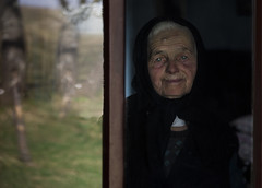 Ana on the window (silvia pasqual) Tags: romania romanian people old age woman face portrait window person elderly eyes blue reflex reflections tradition traditional orthodox travel traveling travelphotography photography photographer lens canon human humanity world soul color colors colorful photo culture europe european portraiture reportage documentary emotion