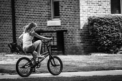 Bicycling (.Chris Lee) Tags: summer blackandwhite bw woman white motion black building brick girl monochrome grass bicycle concrete cycling town movement midwest little pedaling small young sunny monochromatic iowa sidewalk cycle transportation grayscale pedal greyscale nikondx
