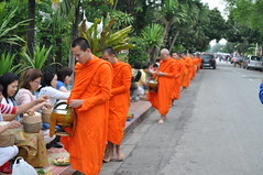 Another monk receives his rations from the faithful (oldandsolo) Tags: southeastasia earlymorning buddhism tourists lp laos luangprabang buddhistmonk laopdr makingmerit unescoworldheritagecity buddhistreligion takbat buddhistfaith morningalmsgivingritualluangprabang morningalmsgivinginluangprabang
