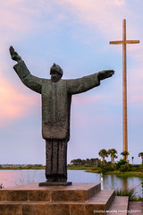 Father Francisco López de Mendoza Grajales statue at sunset, Mission Nombre de Dios, St. Augustine, Florida (DawnaMoorePhotography) Tags: travel sunset usa history tourism statue sunrise religious outdoors coast colorful cross unitedstates florida location tourist historic southern coastal destination thesouth southeast staugustine attraction deepsouth northflorida southeastern sunshinestate saintaugustine missionnombrededios theshrine goldcross northeastflorida floridasfirstcoast donpedromenéndezdeavilés drivanmestrovic fatherfranciscolópezdemendozagrajales shrineofourladylaleche