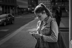 Absorbed (Leanne Boulton) Tags: monochrome people portrait urban street candid portraiture streetphotography candidstreetphotography candidportrait streetportrait streetlife young woman girl female face facial expression mood atmosphere mobile phone hands gesture backlit tone texture detail depthoffield bokeh naturallight outdoor spring sunlight light shade shadow shadows city scene human life living humanity society culture canon canon5d 5dmarkiii 70mm character ef2470mmf28liiusm black white blackwhite bw mono blackandwhite glasgow scotland uk