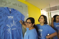 Colleagues taking the pledge to walk healthy by signing the t-shirt
