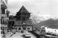 04a3371 18 (ndpa / s. lundeen, archivist) Tags: nick dewolf nickdewolf bw blackwhite photographbynickdewolf film monochrome blackandwhite april 1971 1970s 35mm europe centraleurope switzerland swiss alpine alps graubünden grisons city stmoritz easternswitzerland suisse schweitz citylife candid streetphotography streetlife mountains peaks snow snowy snowcovered building buildings street cars vehicles automobiles parkedcars streets sign signs lesfleurskernen neuesposthotel parking architecture swissalps