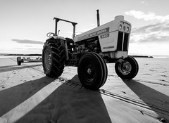 Farmer Brown goes to the beach (ajecaldwell11) Tags: sunrise ankh water tractor light tide newzealand blackandwhite waimarama rocks dawn beach sky boat hawkesbay caldwell waimaramabeach clouds