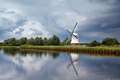 white windmill over clouded sky (Olha Rohulya) Tags: blue summer sky cloud storm holland reflection building nature water netherlands windmill dutch architecture rural river dark landscape outside outdoors countryside canal scenery view scenic dramatic nobody nopeople surface farmland reflect cloudscape