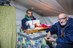 inside the tailors tent (dominic_wenger) Tags: greece sindos thessaloniki athen frakapor refugee refugees refugeecamp camp military crysis borders open world problem swisscross volunter help portrait face family poor man woman kids chil child children beautiful beauty war syria tent tents hall light dark cold candid looking people human humanity sun boring life flee volunteer frame sigma35 sigma canon 5dmk3 lowlight sigmaart inside tailor sewer shaddow sew cloth clothing clothes fix macedoniagreece makedonia