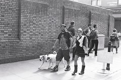 Urban dog walkers on Brick Lane (IanAWood) Tags: london candid streetphotography 35mmfilm bwfilm monochrome fujineopan400cn analoguerangefinder contaxg2 carlzeissplanart452forcontax notwalkingwithmynikon bricklane womeninshortsandboots bootsandskirt ishootpeople istillshootfilm londononfilm 35mmfilmphotography
