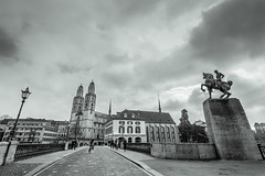Grossmnster Towers, Zurich, Switzerland (ShivRamky) Tags: travel bridge people blackandwhite bw horse travelling tower statue canon river switzerland europa europe suisse cloudy pov swiss zurich sigma overcast cobble cobblestone cycle siva oldtown bnw twintower grossmnster 10mm limmatplatz immat shivramky