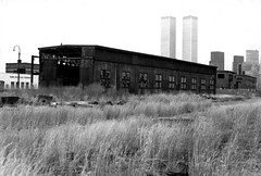 Amber waves of grain, Jersey City style. Several abandoned Central Railroad of New Jersey buildings adorned with discarded tires and broken windows. The World Trade Center and Lower Manhattan hover over the scene across the Hudson. March 1975 (wavz13) Tags: oldphotographs oldphotos 1970sphotographs 1970sphotos oldphotography 1970sphotography vintagephotographs vintagephotos vintagephotography filmphotos filmphotography newyorkphotographs newyorkphotos oldnewyorkphotography oldnewyorkphotos vintagenewyork vintagemanhattan vintagenewyorkphotography vintagenewyorkphotographs vintagenewyorkphotos oldworldtradecenter vintageworldtradecenter twintowers originalworldtradecenter industrial industrialphotos industrialphotography oldfactories railroadphotography vintagerailroads vintagerailroadphotography oldrailroads oldrailroadphotography oldbuildings vintagebuildings 19thcentury depressing bleak noir noire dark abandonedbuildings oldtrainstations vintagetrainstations antiquetrainstations abandonedtrainstations oldtrainterminals vintagetrainterminals antiquetrainterminals abandonedtrainterminals jerseycityphotographs jerseycityphotos oldjerseycityphotography oldjerseycityphotos oldjerseycity vintagejerseycity vintagejerseycityphotography jerseycityhistory urbanphotography urbanphotos urbanscenes cityphotography newjerseyphotographs newjerseyphotos oldnewjersey vintagenewjersey newjerseyhistory gloomy urban grain grainy libertystatepark 110film instamatic surreal