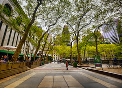 Bryant Park in New York City (` Toshio ') Tags: toshio manhattan newyorkcity newyork bryantpark newyorkpubliclibrary library trees park skyscrapers people path usa america fujixe2 xe2 canopy leaves