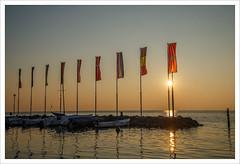 Approdo internazionale (Outlaw Pete 65) Tags: paesaggi landscapes cielo sky tramonto sunset luce light bandiere flags lago lake acqua water barche boats porto harbor nikond600 nikkor24120mm bardolino veneto italia