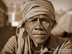 2016-11b Orissa's Ethnic Mosaic (67a) (Matt Hahnewald) Tags: ©matthahnewaldphotography facingtheworld photography photo image frame faceperception physiognomy psychological amazing spectacular outstanding fantastic favourite superior excellent nikond3100 nikkorafs50mmf18g primelens 50mmlens 43aspectratio horizontalformat street portraiture portrait closeup headshot fullfaceview outdoor sunshine highnoonsun sunlight harshnoonsun cultural character personality realpeople humanhead humanface humaneyes facialexpression livedinface wrinkles eyecontact shaved headwrap consent empathy rapport respect encounter dignity ethnicportrait tribal villager adivasi malitribe koraput orissa eastindia ethnic oneperson male oldman posing authentic awesome focused rugged manly experimental sepiaconversion monochrome