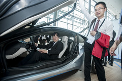 Xiaonian Sun and Cong Li exploring BMW i8 sports car at the cocktail reception