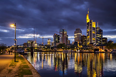 Frankfurt Skyline at Dusk (RickyLoca) Tags: city bridge people urban reflection building water skyline architecture modern night clouds skyscraper river germany lights downtown technology dusk path frankfurt district business hdr frankfurtammain mainhattan