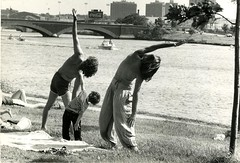 """Two Men and a Child Streching by the Charles River"" (Cambridge Room at the Cambridge Public Library) Tags: colorprintsphotographs basleynancy nancybasley cambridgemass charlesrivermass photography19801990 photographycompetitions"