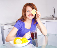 woman drinking tea (hyleysteaonline) Tags: woman female young attractive beautiful home house kitchen table cook make nutrition food meal indoors happy happiness joy joyful cheerful smile caucasian healthy wellness eat diet fruit lemon yellow citrus slice add tea black beverage drink morning immunity vitamins