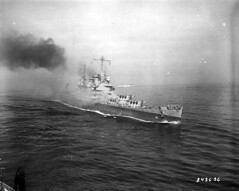 """The cruiser U.S.S. Savannah, on fire and down in the bow on September 11, 1943, after a German radio-controlled bomb, known as a Fritz-X, punched through No. 3 turret and detonated belowdecks, killing more than two hundred sailors. No U.S. Navy warship in World War II would be struck by a larger bomb. One witness reported, """"That hit wasn't natural."""""""