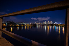 Through the bars of the bridge, looking southward to Minneapolis (evilfoo) Tags: bridge skyline night river spring may minneapolis mississippiriver broadwayavenue mn 2014 natcam